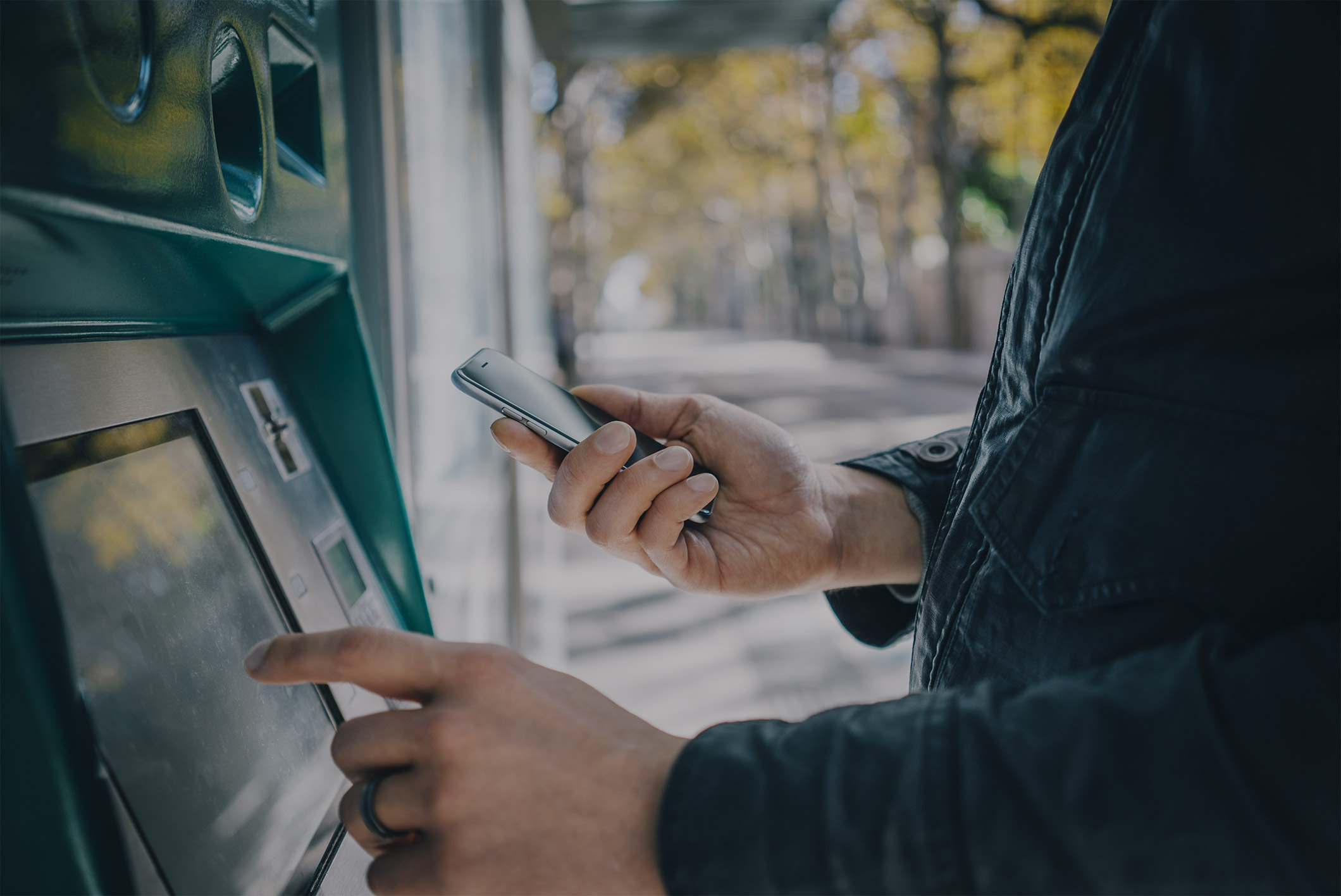 Man using an ATM and a cell phone